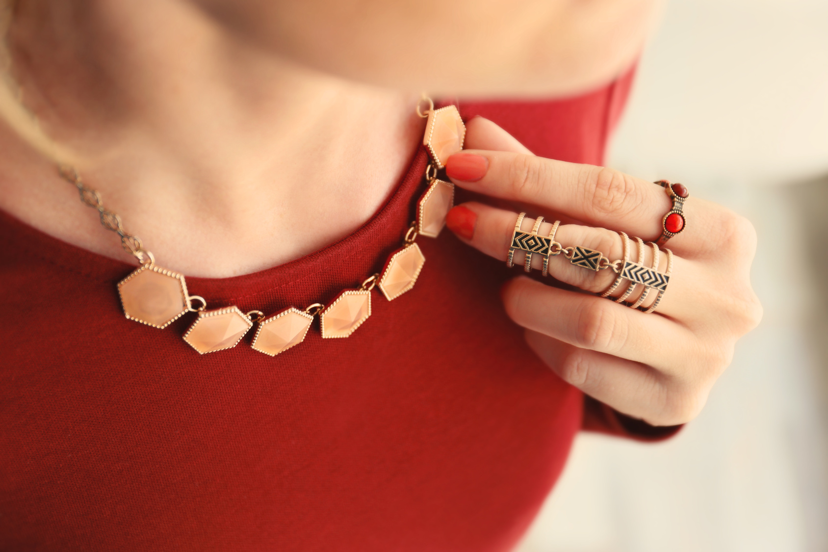 Female hand with beautiful accessories holding necklace, close up